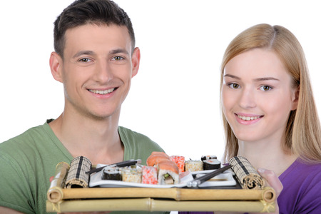 Eating sushi together. Beautiful couple eating sushi while sitting close to each other photo