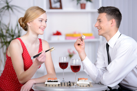 Couple eating sushi. Beautiful young couple sitting together at the restaurant and eat sushi photo