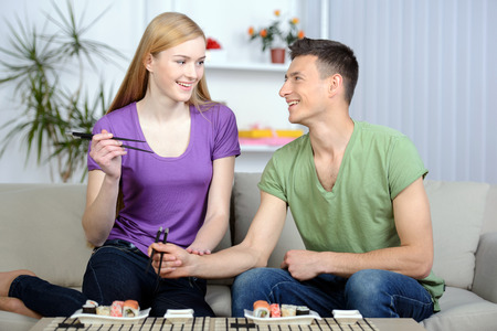 Eating sushi together. Beautiful couple eating sushi while sitting close to each other on the couch photo