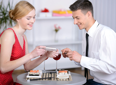 restaurant, couple, technology and holiday concept - smiling couple taking picture of sushi with smartphone camera at restaurant photo