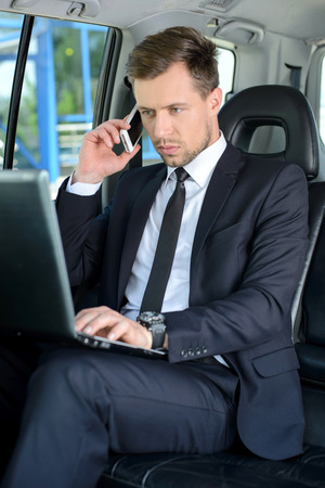 successful businessman: Young successful businessman riding in the car Stock Photo