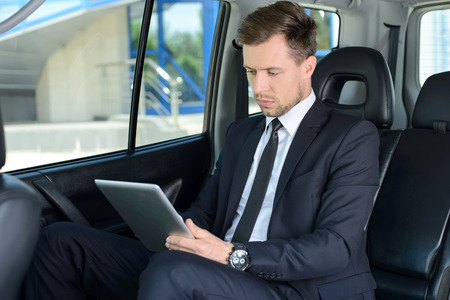 Young successful businessman riding in the car photo