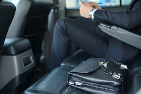 seat: Young successful businessman riding in the car Stock Photo