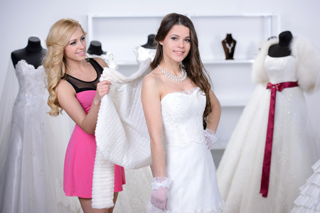 Smiling pretty bride chooses white gown at shop of wedding fashion photo