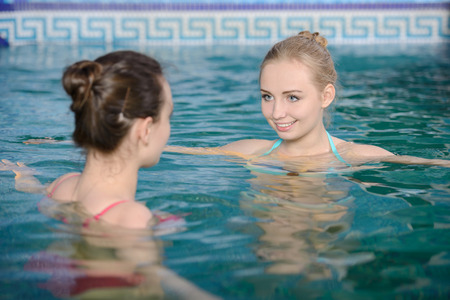Spa And Wellness. Beautiful young woman swimming in the pool. photo