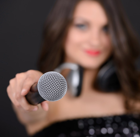 kareoke: Portrait of a young singer with a microphone on a black background Stock Photo