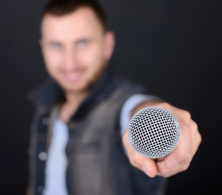 kareoke: Funny man with microphone singing karaoke isolated on a black background