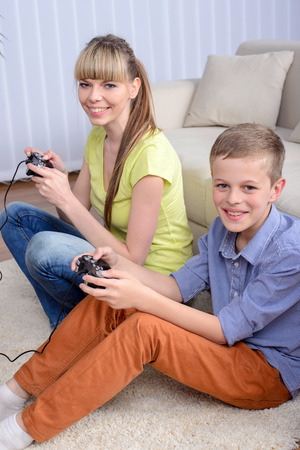 A beautiful woman and her teenage son at home, sitting on a couch playing a video game. photo