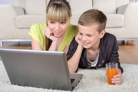 Cheerful boy and mother lying on floor using laptop at home in living room photo
