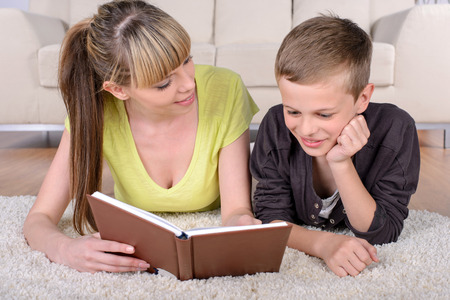Cheerful boy and mother lying on floor using book at home in living room photo