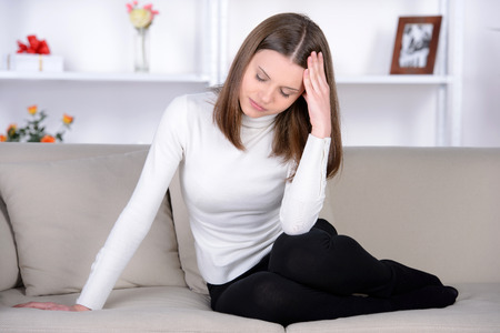 Feeling awful headache. Frustrated young woman holding head in hands and expressing negativity while sitting in bed at her apartment Stock Photo - 28954135