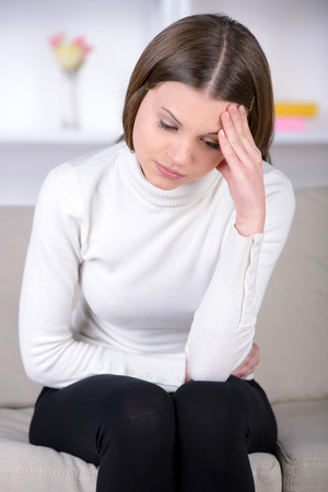 expressing negativity: Feeling awful headache. Frustrated young woman holding head in hands and expressing negativity while sitting in bed at her apartment Stock Photo