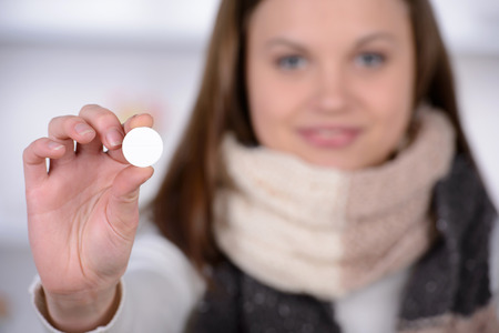 expressing negativity: Woman taking aspirin. Young woman holding pill upon glass with water and expressing negativity while sitting in bed at her apartment