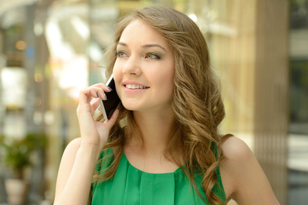 I have got a lot on sale. Beautiful young woman in blue dress holding shopping bags and talking on the mobile phone Stok Fotoğraf