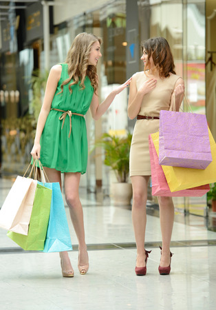 Enjoying shopping. Two beautiful young women shopping together and talking photo