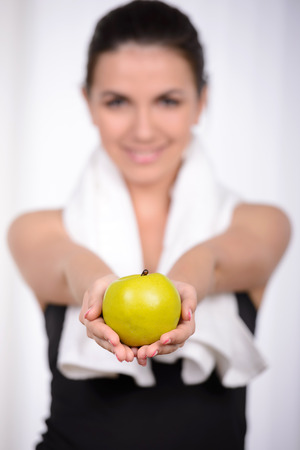Living a healthy life. Beautiful woman in sports clothing throwing an apple up and smiling photo