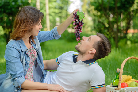 Lovely moments. Young girl feeding her boyfriend with a grapes bunch on the picnic photo