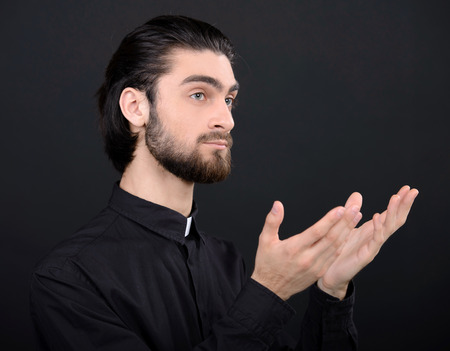Praying priest. Portrait of priest standing isolated on black photo