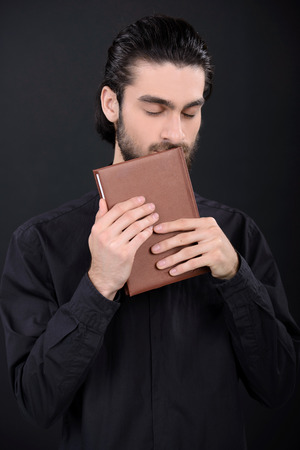 Priest with Holy Bible. Portrait of priest reading the Holy Bible photo