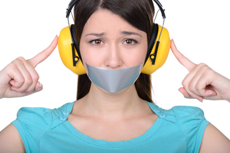 sellotape: It is better to be silent. Upset girl with self-adhesive tape over her mouth and headphones so as not to hear