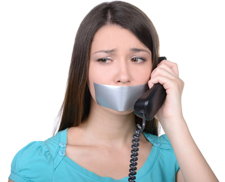 It is better to be silent. Upset girl with self-adhesive tape over her mouth, trying to talk on the phone photo