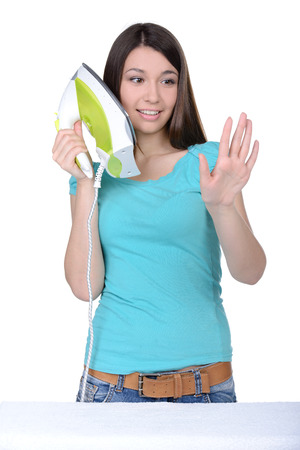 answered: Young woman housewife mistake and answered on the iron, while her phone was ringing Stock Photo