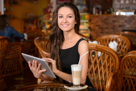 beauty shop: Happy young woman drinking coffee  tea and using tablet computer in a coffee shop Stock Photo