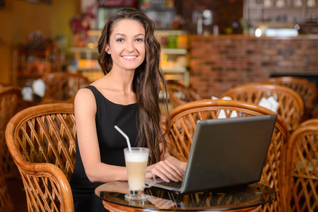 only 1 girl: Young lady browsing the Internet at the cafe Stock Photo