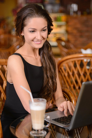 Young lady browsing the Internet at the cafe photo