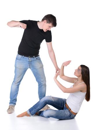 残忍な男は女性を攻撃します。女性の手で彼女の顔を保護します。