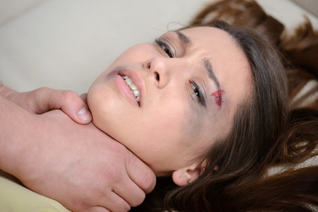 Close up of scared woman being strangled. Fighting with her boyfriend in a bed