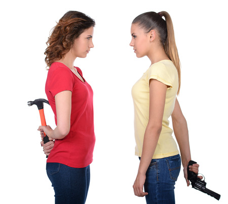 Friendship is over. Two angry women standing back to back and holding their arms crossed while isolated on white photo