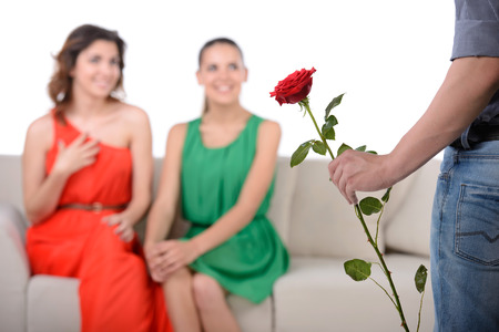 Who to choose? A young man chooses between two girls for the gift of a flower photo