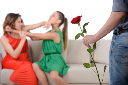 flirting women: Two angry woman fighting for a man, isolated over white background Stock Photo