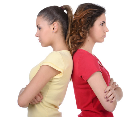 angry face: Friendship is over. Two angry women standing back to back and holding their arms crossed while isolated on white