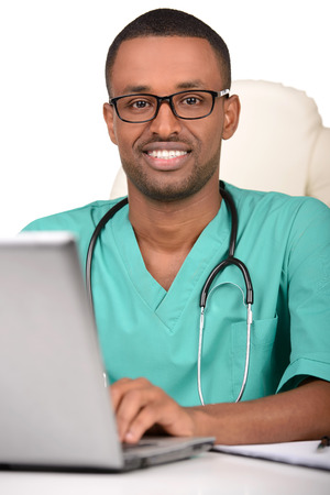 Young successful African American man doctor in consulting room, examining x-ray photos  Studio shot  White background photo