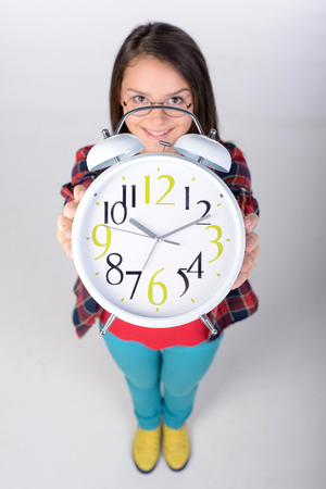 recourse: Portrait of a teenage girl holding a big clock. Upper recourse. Gray background Stock Photo