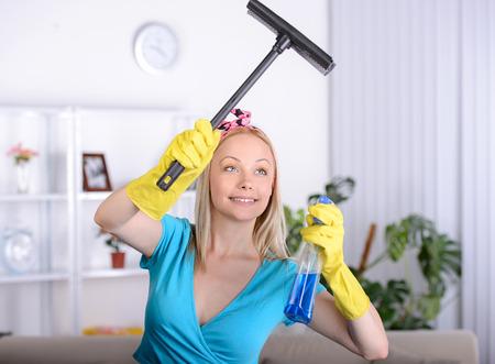 pulizia viso: Bella casalinga pulisce una finestra di casa