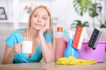 Beautiful housewife drinking tea while cleaning at home photo