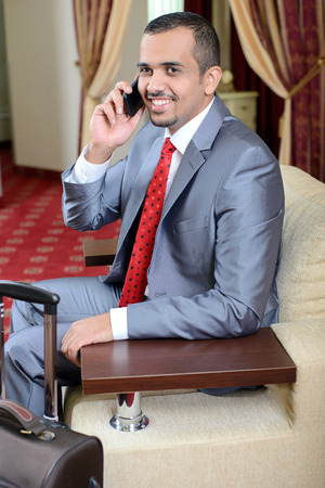 Portrait of Asian businessman with a suitcase, sitting in a chair, talking on the phone in a hotel room photo