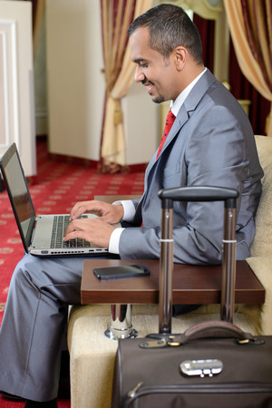 Portrait of Asian businessman with a suitcase sitting in chair using laptop in hotel room photo