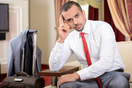 Portrait of Asian businessman with a suitcase, sitting in a chair in a hotel room photo