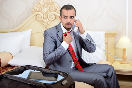 Portrait of Asian businessman with a suitcase, sitting in bed and talking on the phone in a hotel room photo