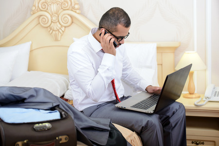 Portrait of Asian businessman with a suitcase, sitting on bed and using laptop in hotel room photo