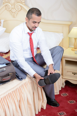 Portrait of Asian businessman with a suitcase, sitting on the bed and take off your shoes in a hotel room photo
