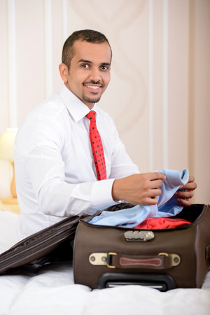 Portrait of Asian businessman with a suitcase, sitting on the bed and makes things up a suitcase in hotel room photo