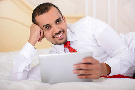Portrait of Asian businessman with a suitcase lying on a bed and using a tablet, in a hotel room photo