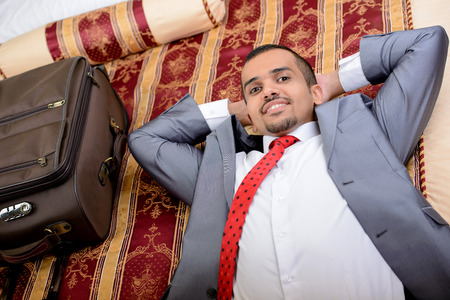 Portrait of Asian businessman with a suitcase lying on the bed in the hotel room photo