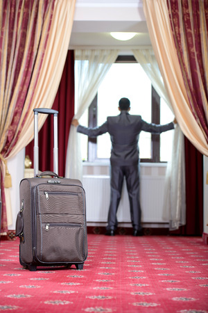Businessman standing at the window, just go to the hotel room photo