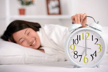 Sleep. Portrait of Asian woman sleeping on the bed at home. Great alarm clock in the foreground Stock Photo